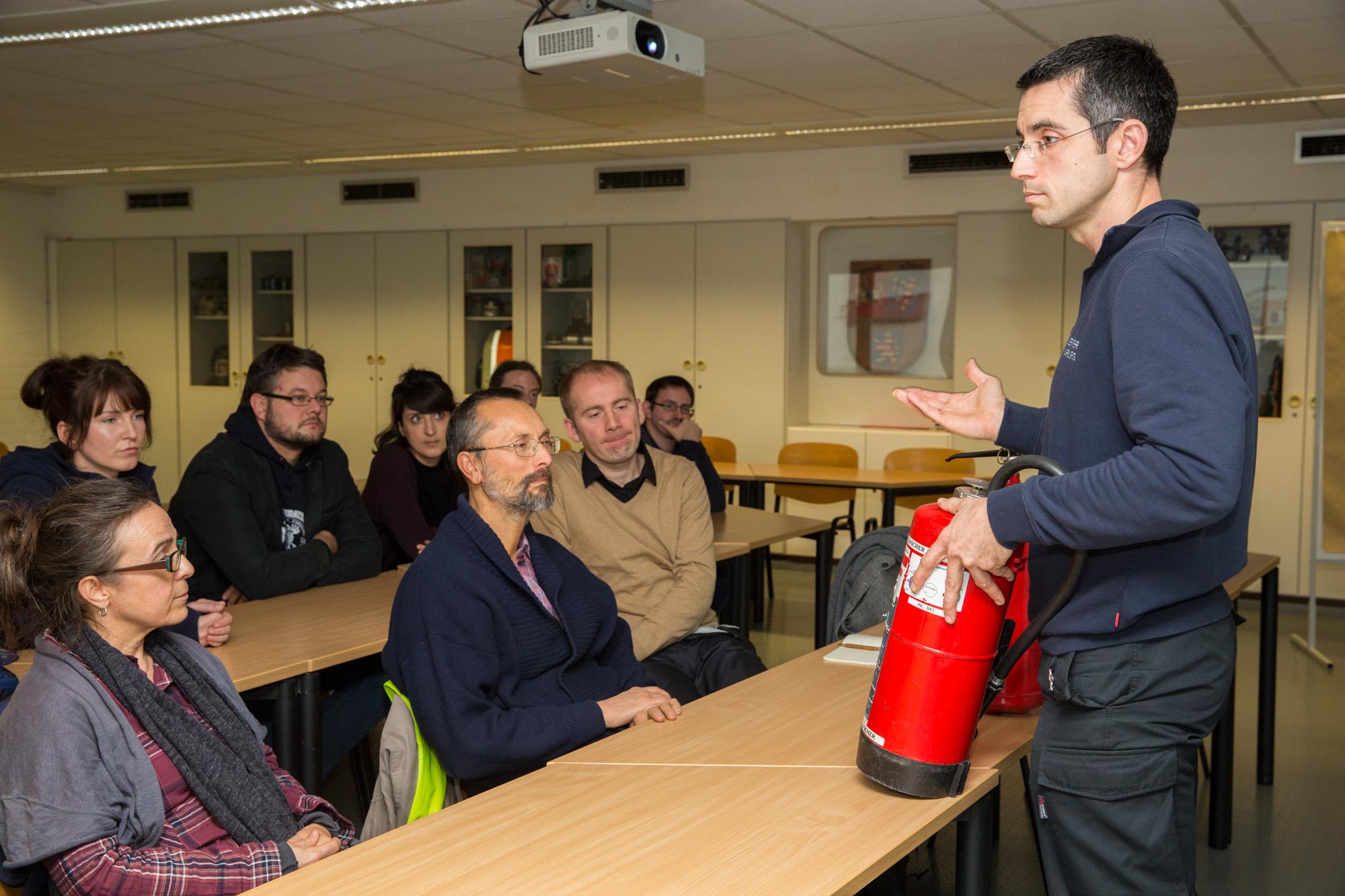 Oberbrandmeister Schmidt erklärt die Benutzung von Feuerlöschern